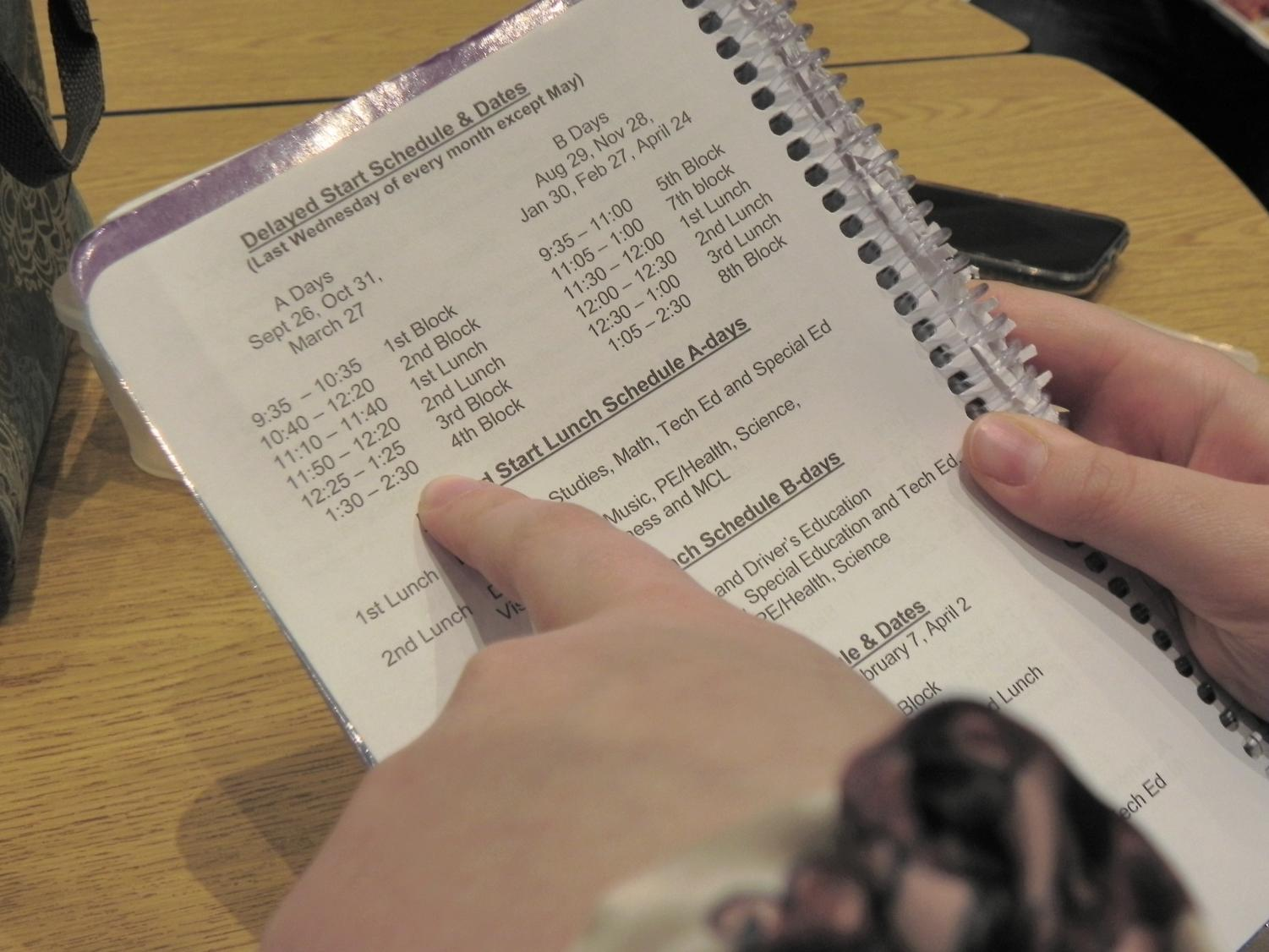Sophomore Lexy Forsythe looks at the late start schedule in her planner, where students can find late start dates, times, and lunch schedules on page 4.
