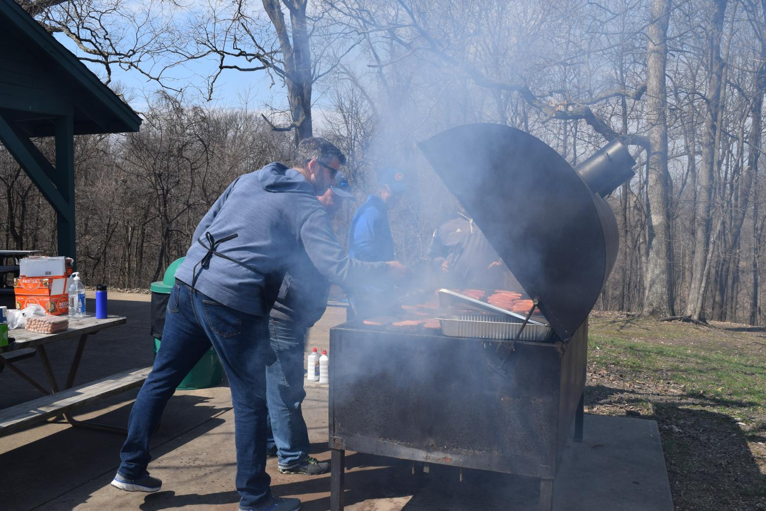 "Science teacher Will Young, athletic director  Mark Proccer, physical education teacher Chris Frankenfield, and business teacher Jim Parks grill food at the senior picnic on April 2. Young said, ""When the wind isn't blowing in my face… this is way better than proctoring the ACT."""
