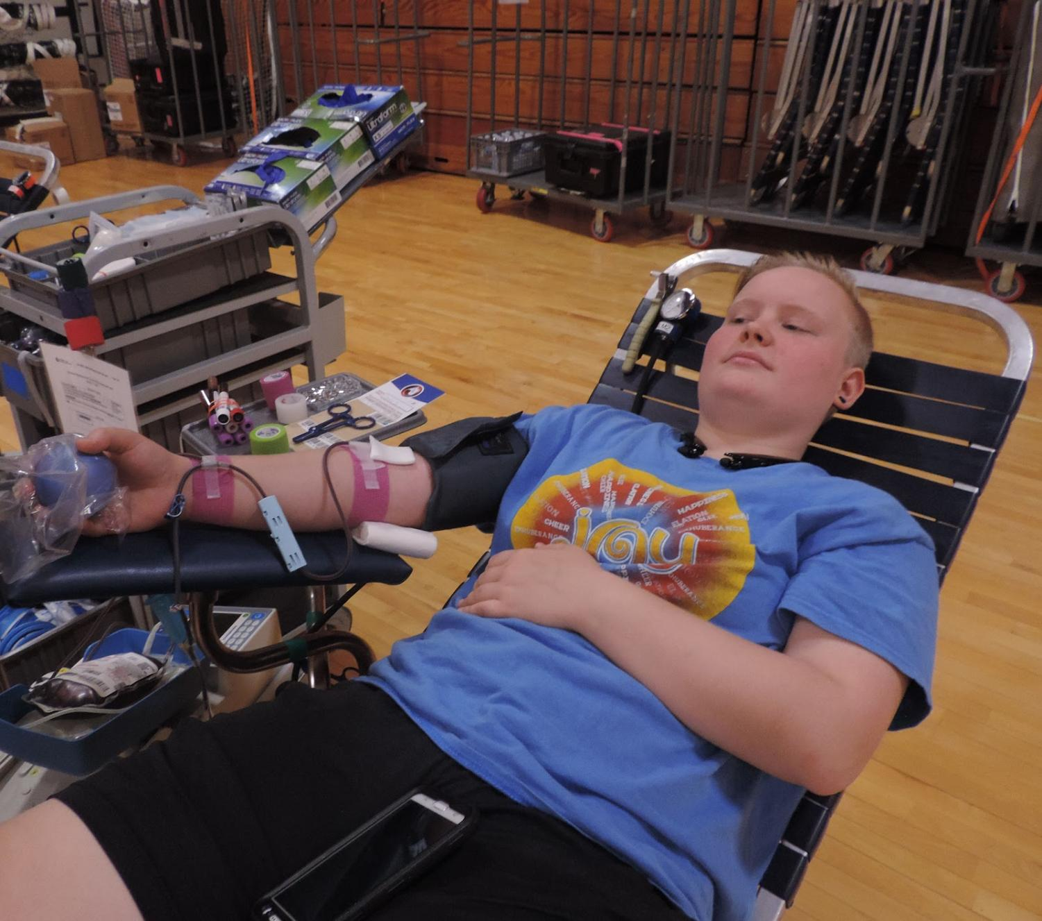 Junior Alex Smothers donates blood on Oct. 28 at 12:00 pm in the upper gym. After the students finish donating blood, they are given snacks, time to rest, and free t-shirts.