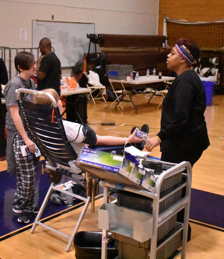 Junior Sierra Dickerson comforts sophomore Alex Smothers while they donate blood. Sophomores must get parental permission to be able donate