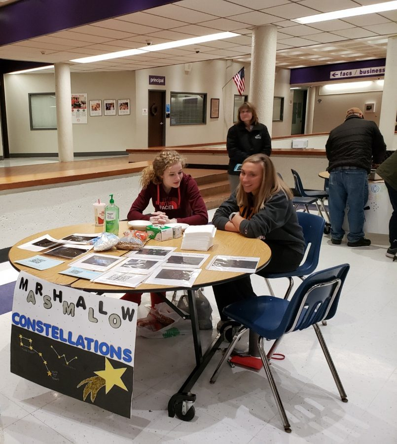 Senior Amy Jordan and and junior Jacquelyn Tope prepare their table for Stargazing Night guests. Their station includes making star constellations out of marshmallows and pretzel sticks or toothpicks, a popular attraction among the younger kids.
