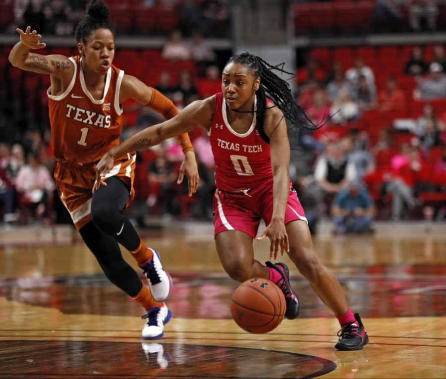 Texas Tech's Chrislyn Carr (0) dribbles the ball around Texas' Sug Sutton (1) during a Big 12 Conference game Sunday at United Supermarkets Arena. [Brad Tollefson/A-J Media]