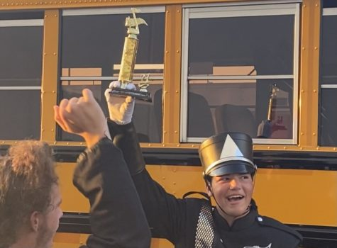 """Placing third overall along with winning the best percussion caption award, senior drum major Duncan Bertier hoists the third-place trophy. """"It felt great, do I think that we should have placed higher? Yes, we should have and we will place higher,"""" said Bertier."""