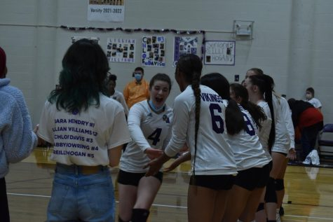 """Senior Gabby Bowring high fives her teammates as they cheer her on during the senior line up. """"We all had so much fun together, we always do but we were all really energetic for this  game,"""" said Bowring."""